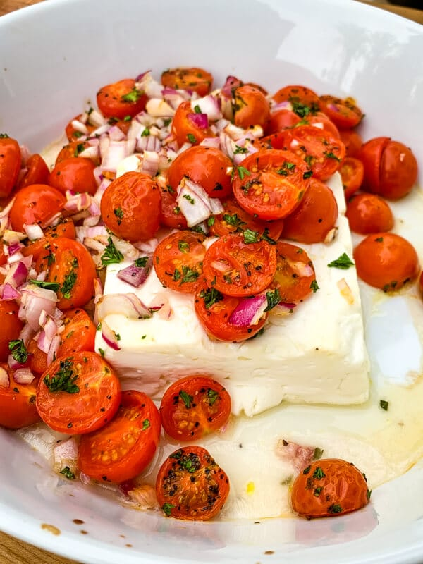This Mediterranean Baked Feta is an irresistible, quick and easy summer appetizer. Pile salty feta with sweet cherry tomatoes and herbs and heat in the oven until warmed throughout. Easy peasy!