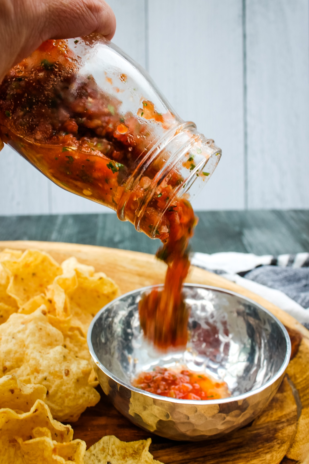 side view of restaurant style salsa being poured into a bowl