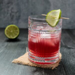Side view of a pomegranate gimlet cocktail garnished with a lime wheel