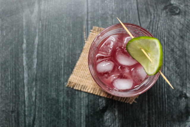 Overhead view of a pomegranate gimlet cocktail garnished with a lime wheel