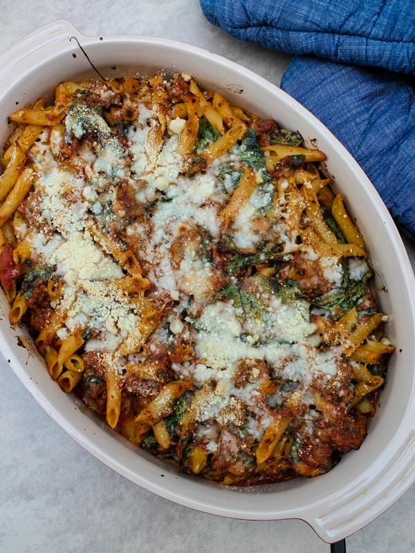 In this Baked Ziti with Sausage & Spinach, spicy Italian sausage, fresh spinach, and a tomato-pesto sauce are tossed with penne or ziti noodles for a flavorful, unique spin on the classic baked ziti recipe. Comfort food at its finest.