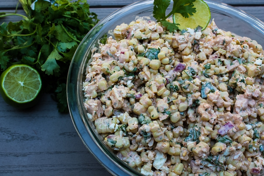 This Mexican Street Corn Salad is a hit at potlucks and BBQs, and always disappears quickly. It is all the best parts of Mexican Street Corn, Elote, but with less mess - grilled corn, a creamy sauce bursting with flavor from spices and fresh herbs, and salty cheese. You and your guests will want seconds!