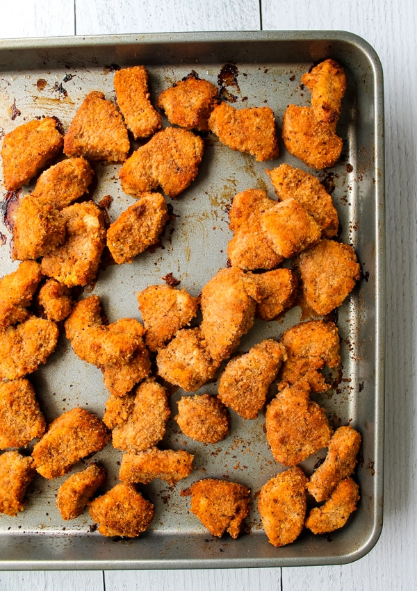 Overhead view of baked buffalo chicken nuggets still on baking sheet, fresh from the oven
