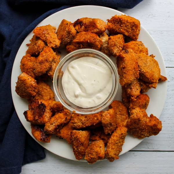 Overhead view of a plate of baked buffalo chicken nuggets with a bowl of blue cheese dressing in the center for dipping.