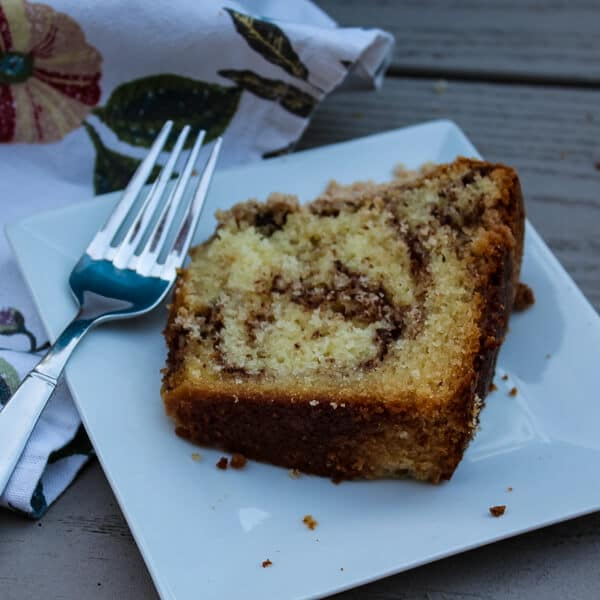 Overhead view of a slice of Sour Cream Coffee Cake with Toasted Pecan Filling, showing off the cinnamon pecan filling swirled through cake, on a small white square plate with a fork.