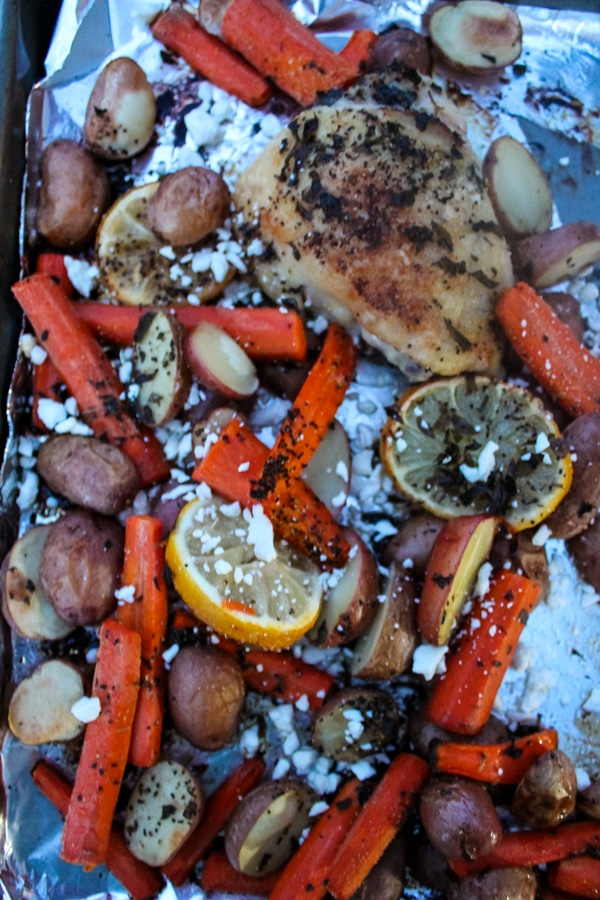 Overhead shot of roasted chicken, potato, carrot on a foil-covered sheet pan, sprinkled with crumbled white feta cheese