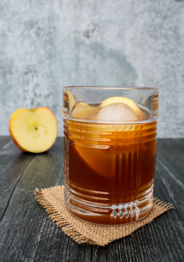 Side view of apple cider old fashioned. Glass set on a square of brown burlap on a black background, with half an apple in the background