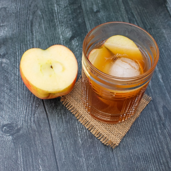 Overhead view of apple cider old fashioned. Glass set on a square of brown burlap on a black background, with half an apple next to the glass