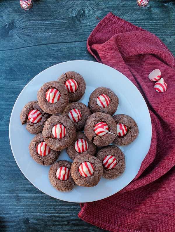 Overhead view of chocolate cookies with candy cane kisses on a white plate. The plate is set on a red cloth on a black background