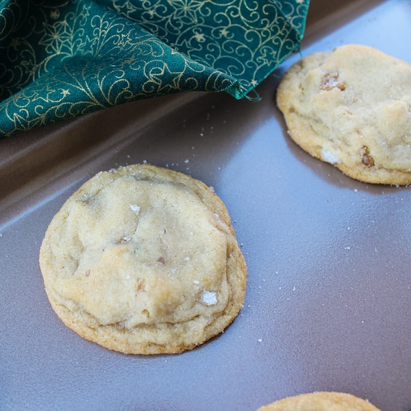 two honey walnut cookies on a baking sheet, with a corner of green and gold cloth slipping onto a corner of the baking sheet