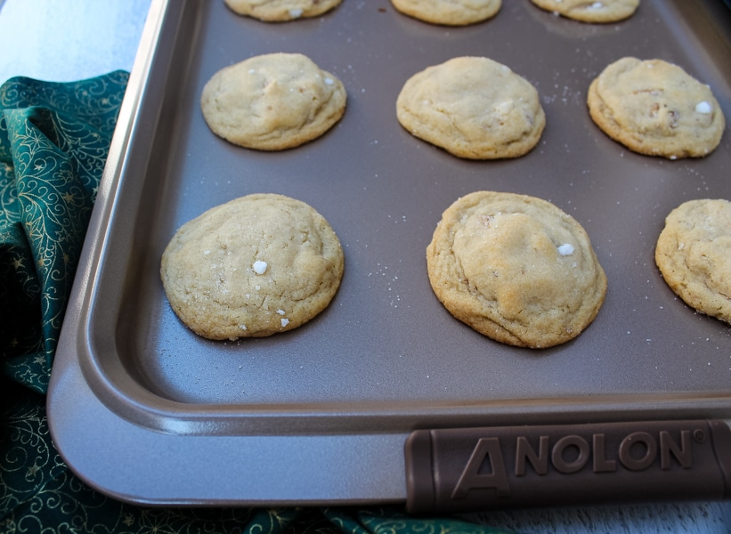 view from above, honey walnut cookies on an anolon baking sheet, sitting on top of green and gold cloth