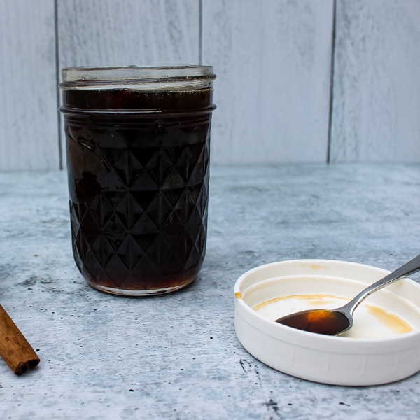side view of a mason jar of Brown Sugar Cinnamon Simple Syrup, with a white lid and spoon