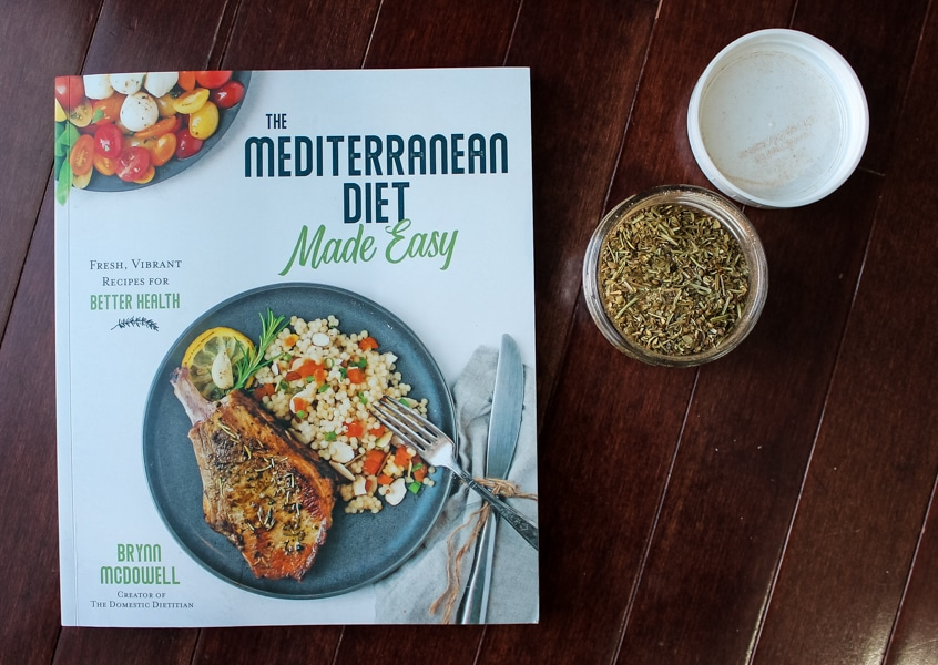 overhead view of Greek Seasoning Spice Blend + Mediterranean Diet Made Easy cookbook on a dark wood background