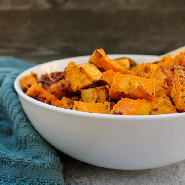 side view of Parmesan & Garlic Roasted Sweet Potatoes in a white bowl