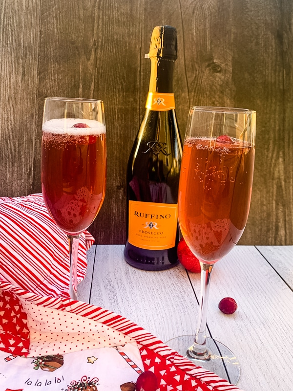 side view of two glasses of Poinsettia Champagne Cocktail and a bottle of bubbly