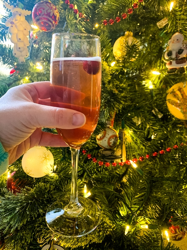 side view of Poinsettia Champagne Cocktail in front of a Christmas tree