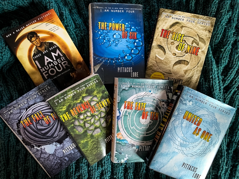 picture of the spines of the 7 books in the Lorien Legacies series by Pittacus Lore