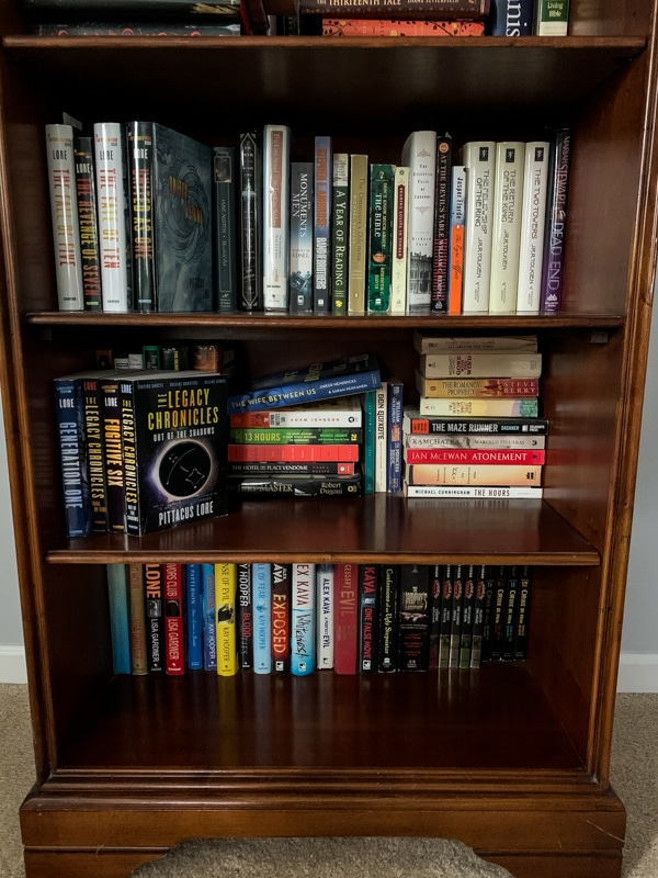 3 shelves of a bookshelf filled with books