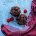 overhead view of two chocolate raspberry muffins on a clear plate