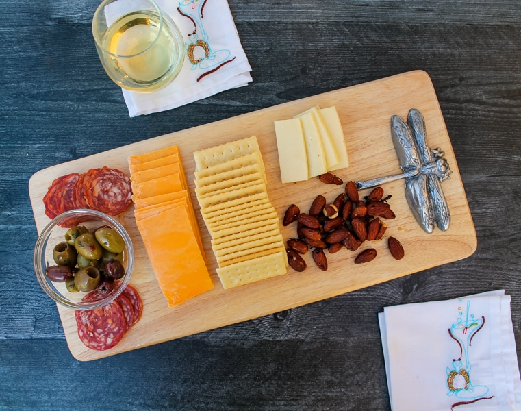 overhead view of a cheese board filled with salami, cheese, crackers, olives, and honey & rosemary almonds