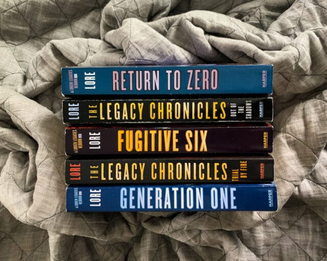 overhead view of the spines of the books in the Lorien Legacies: Reborn and The Legacy Chronicles series