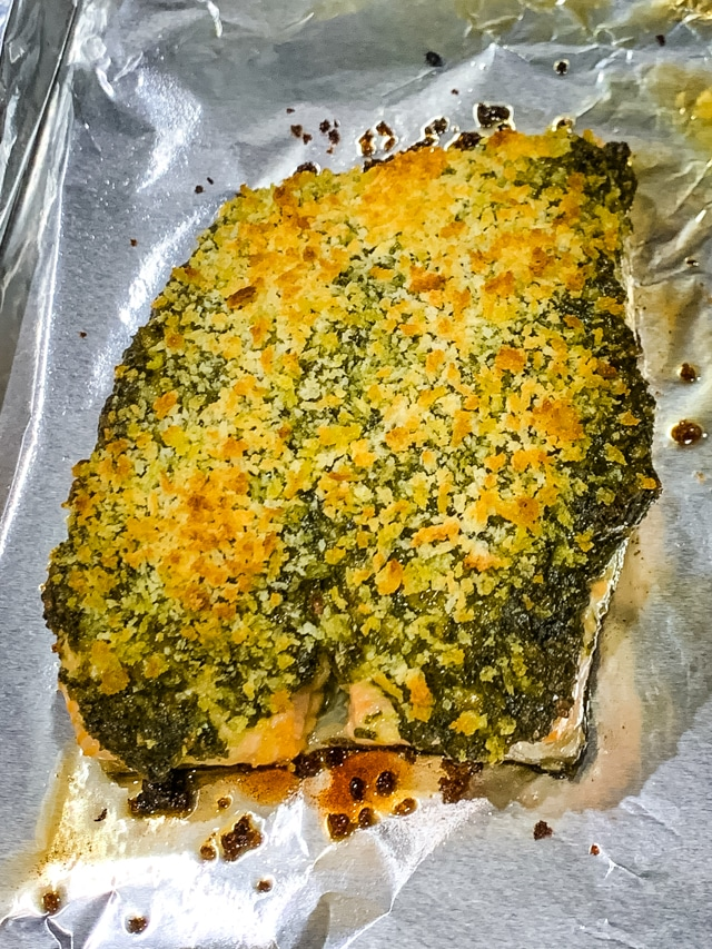 uncut pesto crusted salmon on a foil lined baking sheet