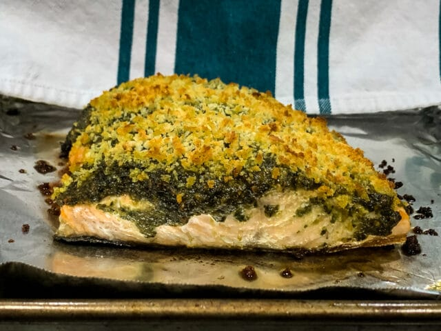 side view of pesto crusted salmon on a foil lined baking sheet
