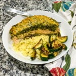 overhead view of pesto crusted salmon in a white bowl with couscous and zucchini