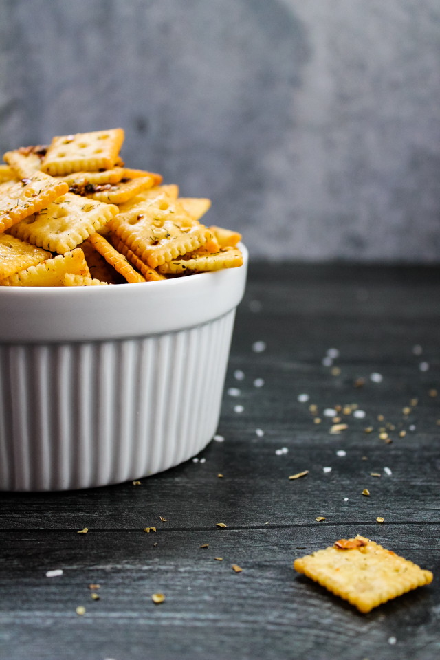 side view of a white bowl filled with spicy seasoned crackers