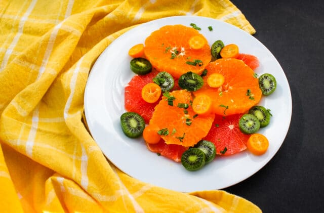 overhead view of citrus & mint fruit salad on a white plate