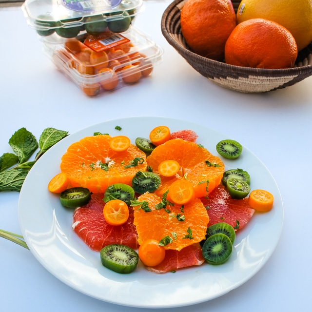 Citrus & Mint Fruit Salad on a white plate with extra fruit in the background