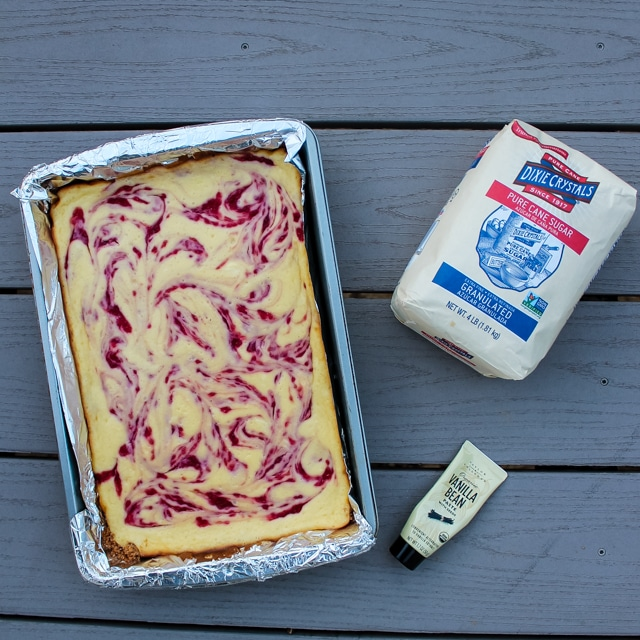 overhead view of a pan of raspberry cheesecake bars with sugar and vanilla paste