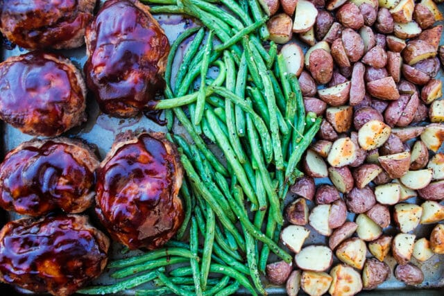 overhead view of individual BBQ meatloaves, green beans and roasted potatoes on a sheet pan