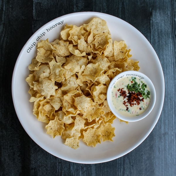 overhead view of queso topped with crumbled chorizo, amongst a large white serving bowl of tortilla chips