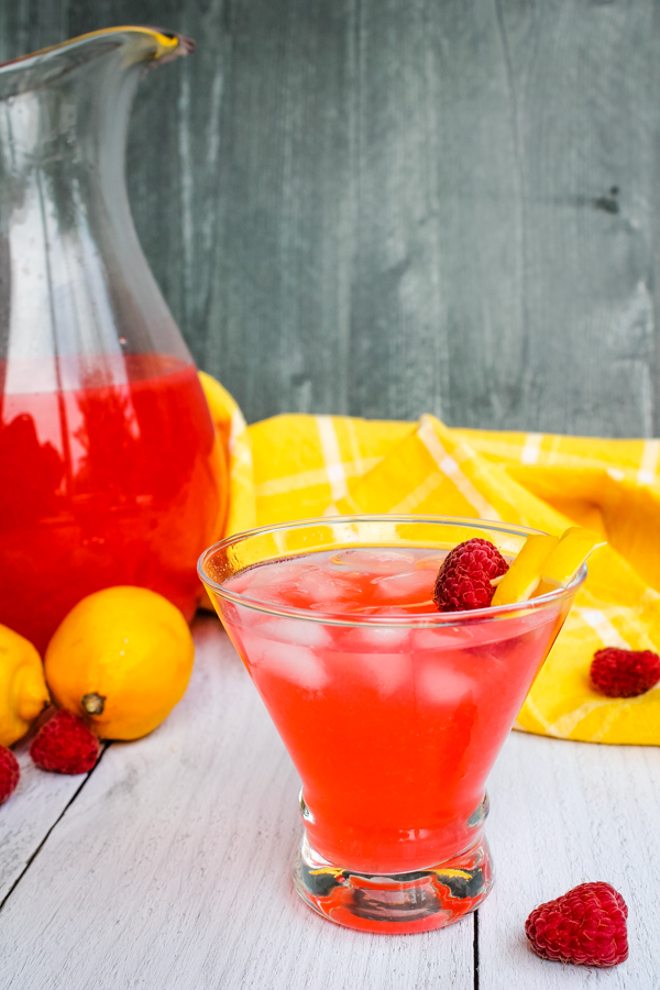 Side view of a glass of Raspberry Lemonade Limoncello Cocktail with a pitcher of the cocktail in the background
