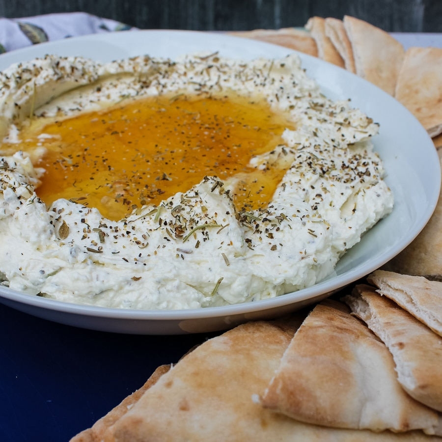 side view of Whipped Feta with Honey on a white plate, surrounded by pita slices