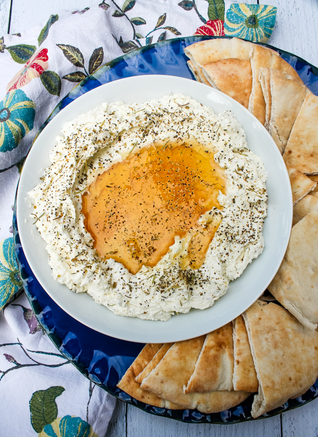 overhead view of Whipped Feta with Honey on a white plate, surrounded by pita slices